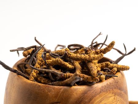 Cordycep sinensis (CHONG CAO) oder Pilz Cordyceps auf Holzschale auf isoliertem Hintergrund hautnah. Medizinische Eigenschaften bei der Behandlung von Krankheiten. Nationale organische Medizin.