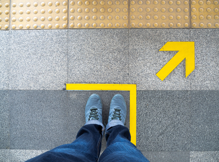Top view of man feet standing over Arrow symbol on subway platform. Yellow arrow sign on floor at the train station.