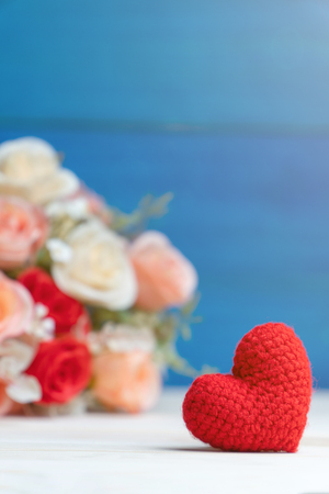 Valentines day concept. hand make yarn red heart in front of rose flower bouquet on wooden table and blue background