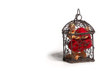 Action figure sitting in cage and holding red heart on white background. Concept of Love and imprisonment Фото со стока