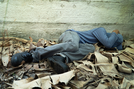 Homeless wore a gray hat and gray long-sleeve shirt. Is sleeping because of exhaustion, with the back leaning against the wall Imagens