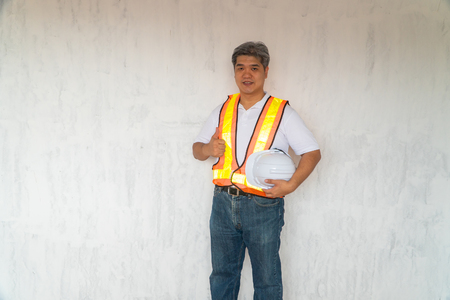 Asian professional engineer working in house construction site for inspection of the cottage under construction and lift the thumb up. Stock Photo