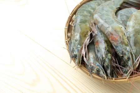 close up group of fresh raw pacific white shrimp in bamboo bowl on wooden table.