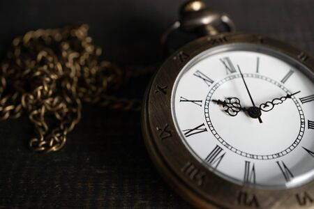 Close Up Antique pocket watch Placed on a black wooden background. copy space for text