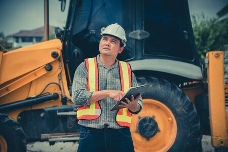 Engineering wearing a white safety helmet standing in front of the backhoe Looking at home construction work And use the tablet to check the blueprint with construction Фото со стока