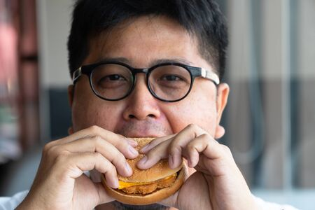 Asia man is eating hamburger in a fast food restaurant and enjoying delicious food. man in a White t-shirt and glasses holding a burger and enjoying the taste of hamburger Фото со стока