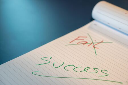 Fail text with a hand with a red pen And crossed out with a green pen on the notebook. Success message by hand with a green pen below the fail. The concept of not giving up on failure.