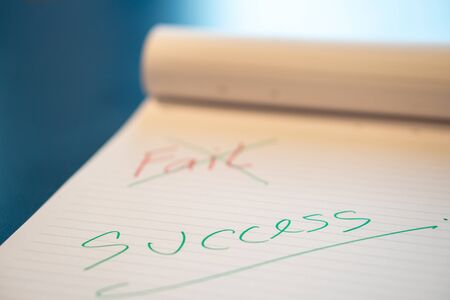 Fild text with a hand with a red pen And crossed out with a green pen on the notebook. Success message by hand with a green pen below the fail. The concept of not giving up on failure.