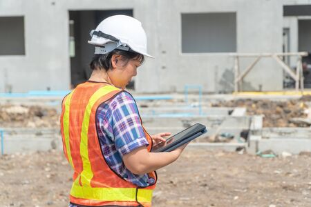 Asian women engineering holds a tablet for use in the inspection of construction sites for accuracy and in accordance with the plan. Concept of Equal rights between men and women