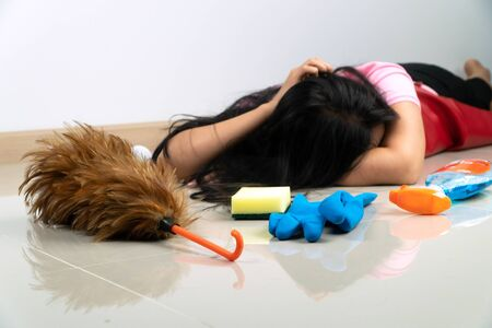 Selective focus of Feather duster. Asian housewives lie on the floor due to fatigue from household chores. With various cleaning equipment placed around