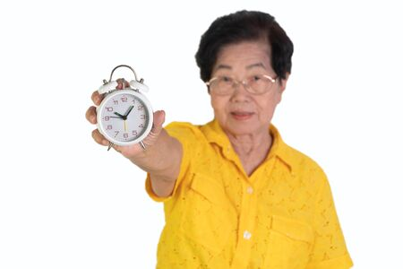 Asian elderly woman holding a white alarm clock on isolated background. The concept aging society That needs time and grandchildren to come back to caring for health care Фото со стока
