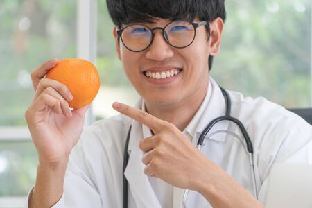 Doctor or nutritionist hold orange and Point your finger at the orange. in and smile in clinic. Healthy diet. Concept of nutrition food as a prescription for good health, fruit is medicine