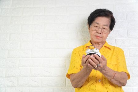 Asian elderly woman holding a white alarm clock, here face shows anxiety. The concept aging society That needs time and grandchildren to come back to caring for healthcare