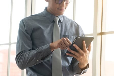 Happy young business man using digital tablet and smiling, standing near the window in office