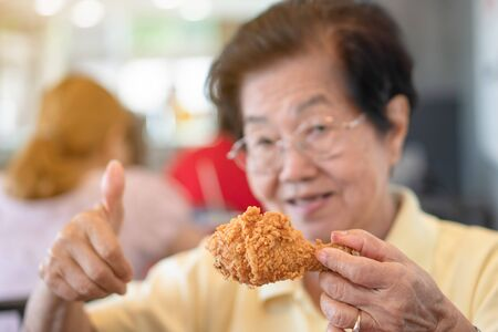 Selective focus of fried chicken, Asian elderly women are eating fried chicken. In the restaurant, lift the thumb. Concept of aging society, Preparedness After retirement And living a happy life. Фото со стока