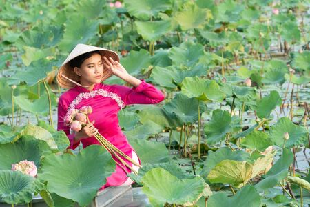 Beautiful asia women wearing white pink traditional Vietnam dress (Ao Wai) and Vietnam farmers hat and sitting on wooden boat in flower lotus lake. Her hands holding lotus flowers. Фото со стока
