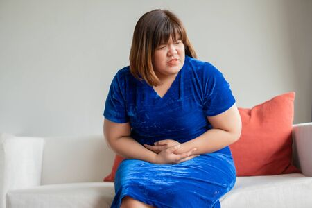 Oversize asian woman sitting on sofa in living room. Her upset and unhappy and holding hands on stomach suffering from abdominal pain. Concept of period cramps, gastritis and health care