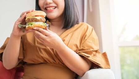 Hungry overweight woman smiling and holding hamburger and sitting in the living room, her very happy and enjoy to eat fast food. Concept of binge eating disorder (BED).