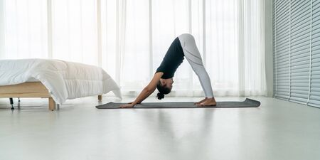 Middle aged women doing yoga downward facing dog pose to meditation with yoga in bedroom at the morning, adho mukha svanasana pose. Concept of exercise and relaxation in the morning.