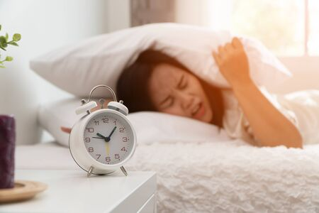Sleepy asian woman sleeping on the bed and use a pillow to close the ear so as not to hear the alarm clock in bedroom. Concept of Lazy day and want to sleep And do not want to wake up in morning Фото со стока