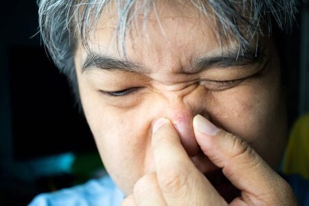 Asian people are squeezing the pimples and blackheads and acne scars on his nose.