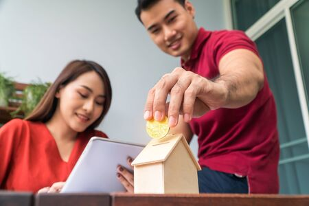 Selective focus of golden coin. Happy Asian couples smiling Because it is profitable from investment And have savings for buying a home and accommodation. Investment concepts and financial planning