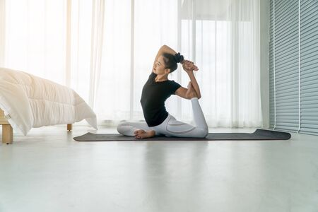 Middle aged women doing yoga in bedroom at the morning, adho mukha svanasana pose. Concept of exercise and relaxation in the morning.