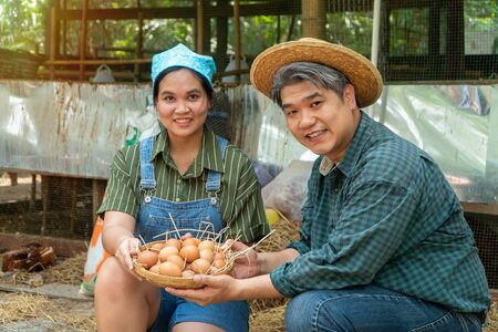 Asian couple farmer holding fresh chicken eggs into basket was sitting near hen beside chicken farm.Smiling because happy with the products from the farm. Concept of Non-toxic food Фото со стока