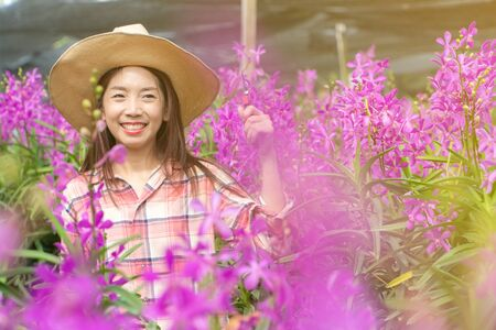 young female gardeners wear a plaid shirt and wear a hat. Hands holding scissors for cutting orchids and smile. new generation farmer, gardeners concept.