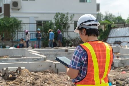 Portrait of Asian woman construction engineer worker with helmet on head using tablet while standing on construction site. building site place on background. Construction concept