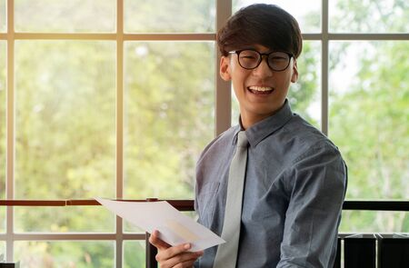 Young Asian businessman excited happy and celebrating success in the workplace after see finalizing the annual sales report. Concept of new entrepreneur successful
