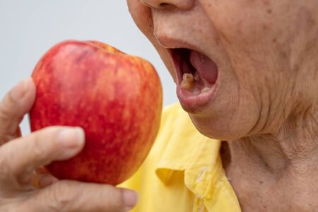 An old woman wears glasses and without teeth trying to eat red apples. Concept of Dental health problems, Elderly patients medical and healthcare concept