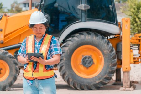 Woman Engineering wearing a white safety helmet standing In front of the backhoe And are using tablet to check the blueprint with construction Фото со стока