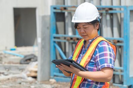 Asian women worker and engineer on building site using tablet for checking the accuracy in places before building and houses. Фото со стока