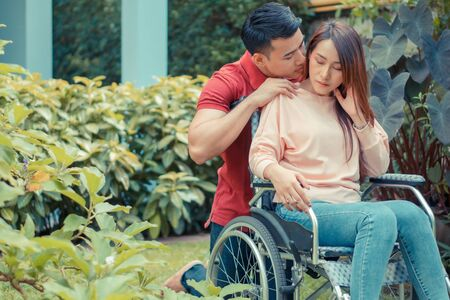 Asian woman in a wheelchair and Unhappy and painful. A Man standing behind the wheelchair and is encouraging his wife, whose feet hurt her leg due to an accident. Concept of caring and support Фото со стока