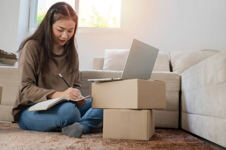 Young entrepreneur, Sitting on the floor and working at home. Checking orders from customers by laptop and writing customer address deliver shipment online sales. Concept of small business owner.