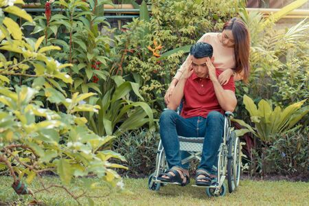 Asian Man in a wheelchair and Unhappy and painful. A woman standing behind the wheelchair and is encouraging her husband, whose feet hurt his leg due to an accident. Concept of caring and support Фото со стока