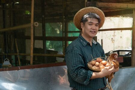 Asian farmer holding fresh chicken eggs into basket and hen was standing near hen beside chicken farm.Smiling because happy with the products from the farm. Concept of Non-toxic food
