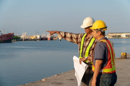 Two engineers stood wearing a safety helmet. Standing at the pier And holding the blueprint And consult the plan In the construction. Concept of efficient construction management.