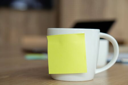 A white coffee cup with a blank yellow sticky note on the cup. Resting on the desk and laptop is placed on the back.