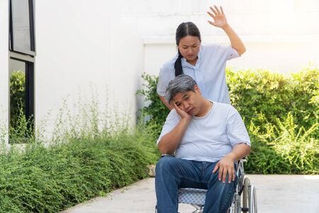 The wife was pushing the wheelchair for her husband. With her raised hands pretending to hit him. Because of being bored with her sick husband and refusing to take care of herself Фото со стока
