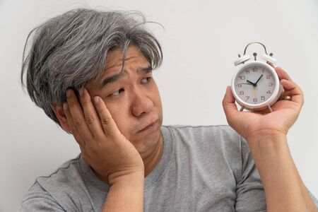 Asian middle-aged man is holding a white alarm clock and his face showed boredom and feeling bad, his problem is a sleep disorder. The concept of suffering insomnia