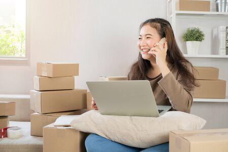 Heureux jeune entrepreneur asiatique, parlant sur le smartphone avec le client pour la commande, Elle sourit pour le succès des ventes au bureau à domicile, Concept de commerce en ligne et de commerce électronique