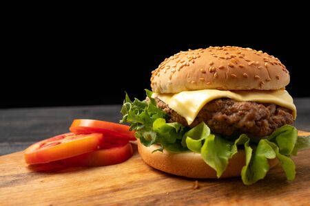fresh tasty homemade hamburger with fresh vegetables, lettuce, tomato, cheese beside sliced tomatoes on a cutting board. Free space for text Stock fotó