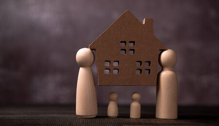Wooden figures family standing and bear wooden house to Protect and burden the problems to protect the family. The concept of Protection and safety, Home Security, property insurance and house. Banque d'images