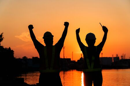 Silhouettes of worker and engineer Raising the hand up and standing on the shipyard. Background is oil storage silo. Teamwork cooperation And success in working together concept.