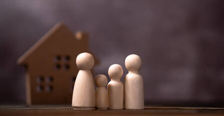 Wooden figures family standing in front of a wooden house. The concept of Protection and safety, Home Security, property insurance and house.