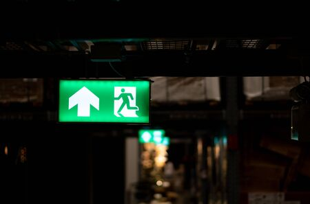 Green fire escape sign hang on the ceiling in the Warehouse. The concept of fire escape training and preparation for evacuation