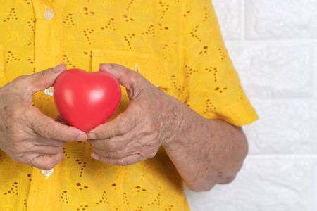 Elderly asian woman holding red heart. Concept of Loneliness and needs to be cared for by children and close ones. Love and care Is something that the elderly want Stockfoto