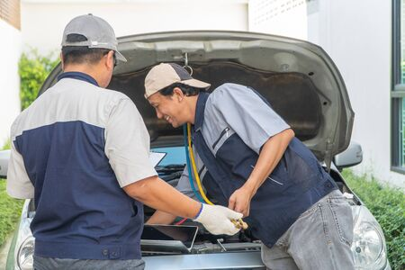 two Auto repairman checks the engine and cooling system before traveling on a long holiday. Concept of Car care and maintenance from experts, Coaching, and advice For practicing a car from an expert Foto de archivo